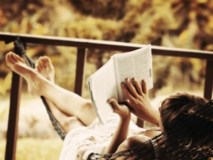 Woman-lying-in-a-hammock-in-a-garden-and-enjoying-a-book-reading